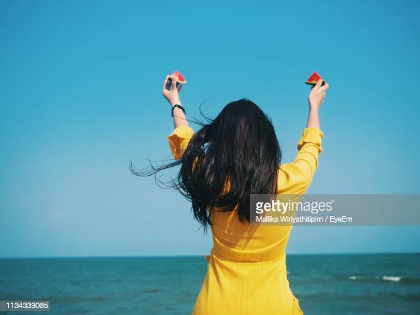 rear view of young woman with arms raised holding melon slices while standing by sea against clear blue sky - cheveux noirs photos et images de collection