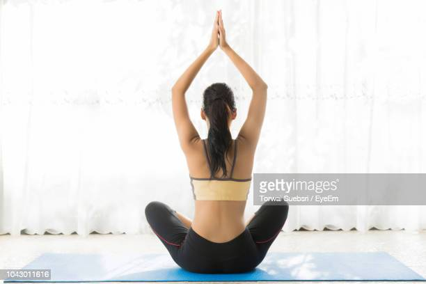 rear view of young woman with arms raised meditating while sitting against curtain at home - torwai stock pictures, royalty-free photos & images