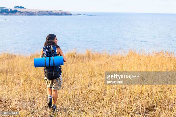Rear view of young woman with backpack hiking in nature