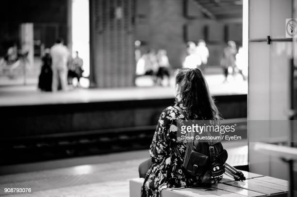 Rear View Of Young Woman With Backpack Sitting At Railroad Station Platform