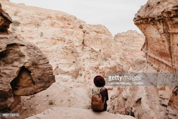 rear view of young woman with backpack sitting on rock at desert against sky - remote location stock pictures, royalty-free photos & images