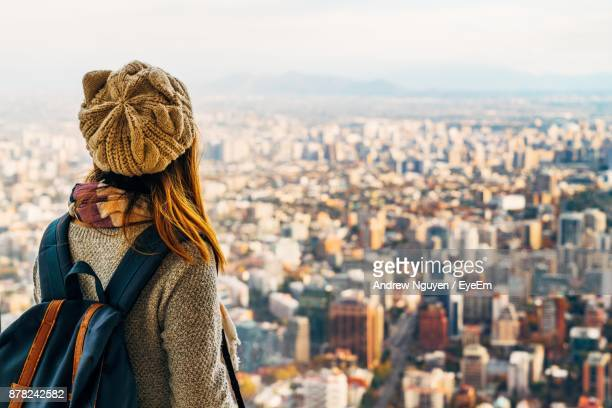 rear view of young woman with backpack standing against cityscape - santiago chile fotografías e imágenes de stock