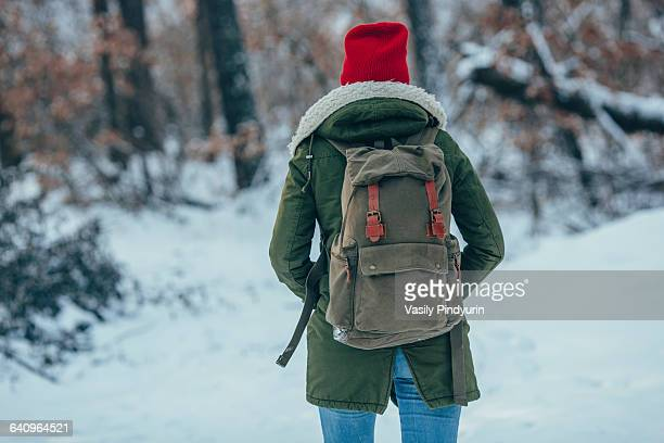 Rear view of young woman with backpack standing on snow covered field