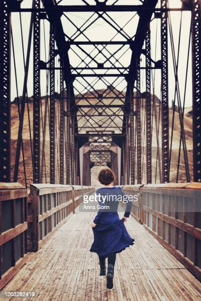 rear view of young woman with braided red hair wearing long-sleeved vintage blue dress running down old railroad bridge - long dress stock pictures, royalty-free photos & images