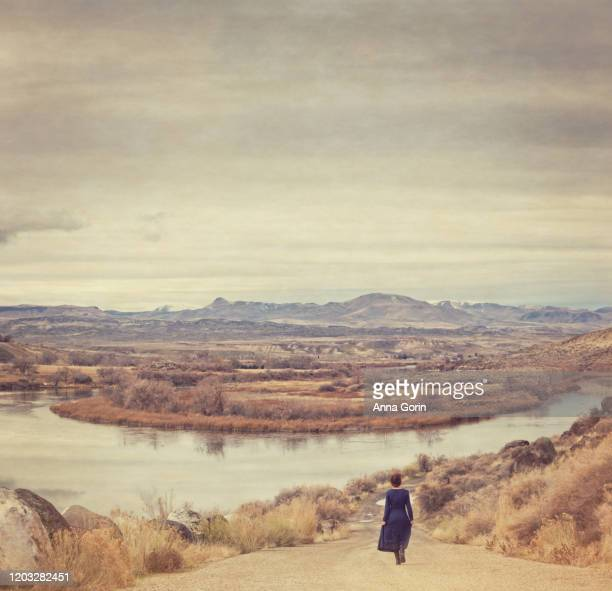 rear view of young woman with braided red hair wearing long-sleeved vintage blue dress walking down country road toward river and mountains,toned effect with vintage texture - look down stock-fotos und bilder