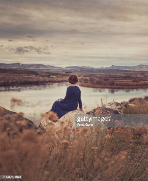 rear view of young woman with braided red hair wearing long-sleeved vintage blue dress sitting on rock overlooking river, toned image with textured effect - long dress stock pictures, royalty-free photos & images