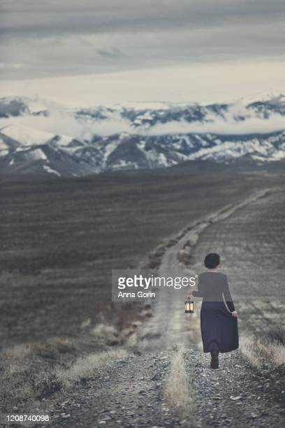 rear view of young woman with braided red hair wearing long-sleeved vintage blue dress and carrying lantern, walking down dirt road toward snow-covered mountains at dusk, vintage toning - hero and not superhero stock pictures, royalty-free photos & images