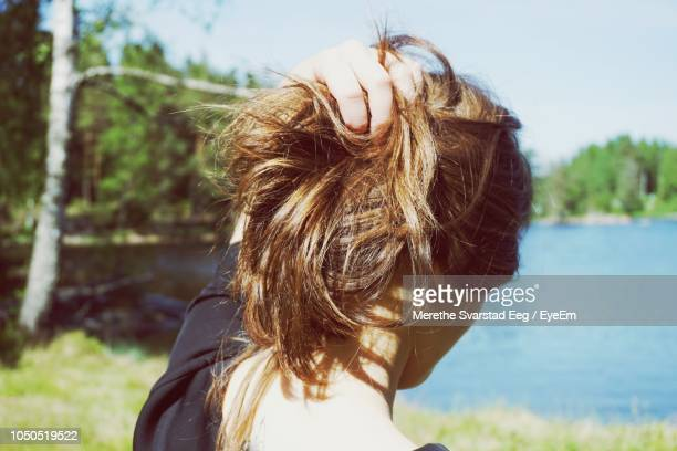 rear view of young woman with hand in hair standing at lakeshore against sky - femme brune de dos photos et images de collection
