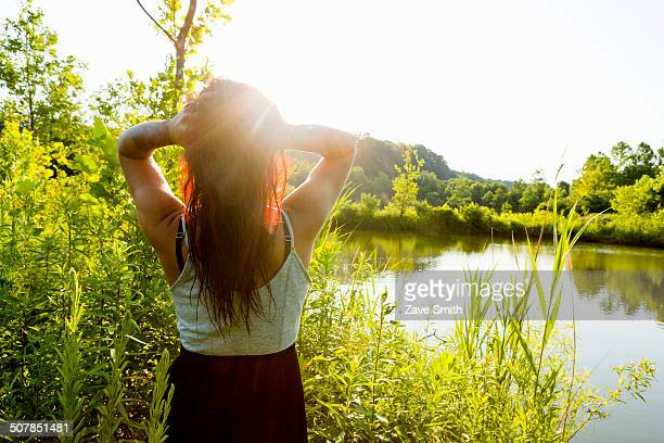 Rear view of young woman with hands in hair in sunlight, Delaware Canal State Park, New Hope, Pennsylvania, USA