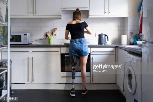 rear view of young woman with leg prosthesis in kitchen at home - amputee woman stock-fotos und bilder