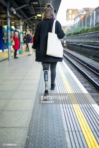 rear view of young woman with leg prosthesis walking at station platfom - トートバッグ ストックフォトと画像