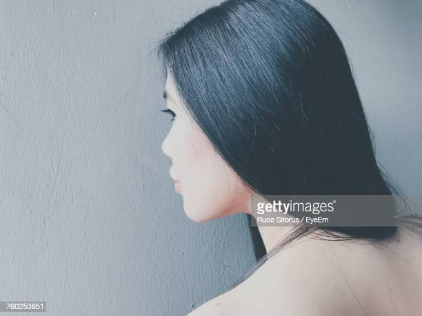 Rear View Of Young Woman With Long Hair Against Wall