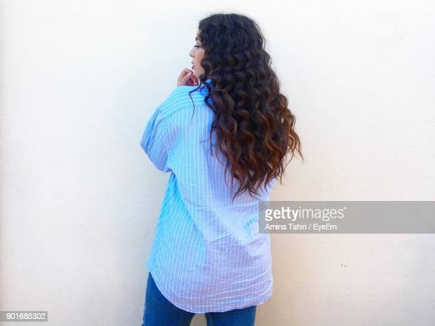 Rear View Of Young Woman With Long Hair Standing Against White Wall