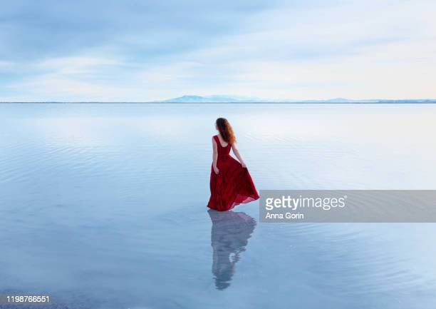 rear view of young woman with long wavy red hair in sleeveless red dress walking in shallow still lake - red dress stock pictures, royalty-free photos & images