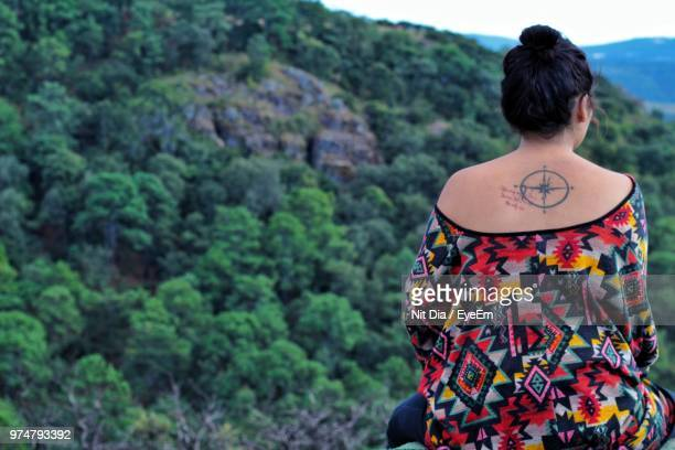 Rear View Of Young Woman With Tattoo On Back Sitting Against Trees