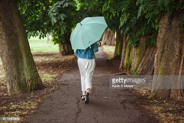 rear view of young woman with umbrella strolling in park - green skirt stock pictures, royalty-free photos & images