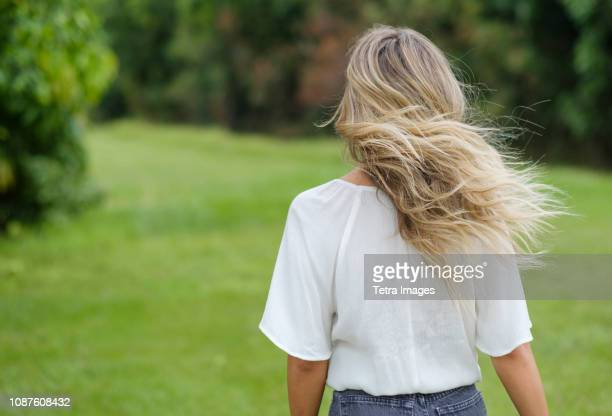 rear view of young woman with windswept hair - blonde hair stock pictures, royalty-free photos & images