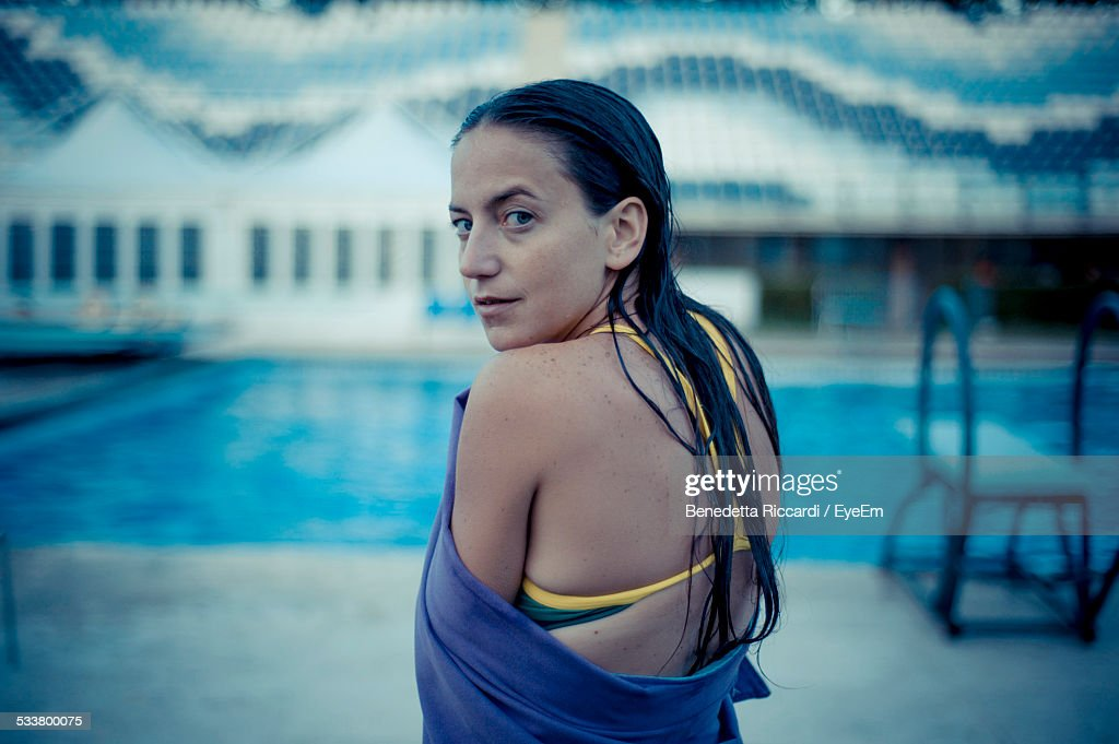 Rear View Of Young Woman Wrapped In Towel, Standing On Poolside : Foto stock
