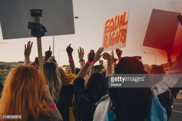 rear view of young women protesting for equal rights while marching in city - protestor stock pictures, royalty-free photos & images