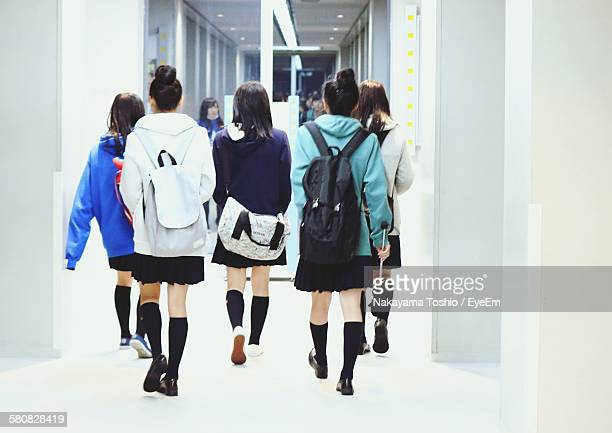 Rear View Of Young Women Walking On Corridor At University