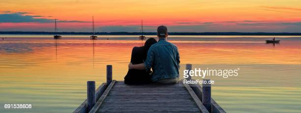 rear view on young couple sitting side by side on jetty looking at reflection of orange sky reflection on lake - light natural phenomenon stock pictures, royalty-free photos & images
