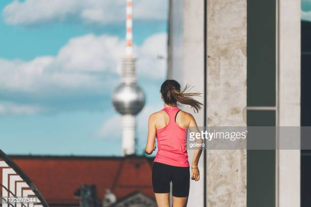 rear view on young sports woman running in berlin - central berlin stock pictures, royalty-free photos & images