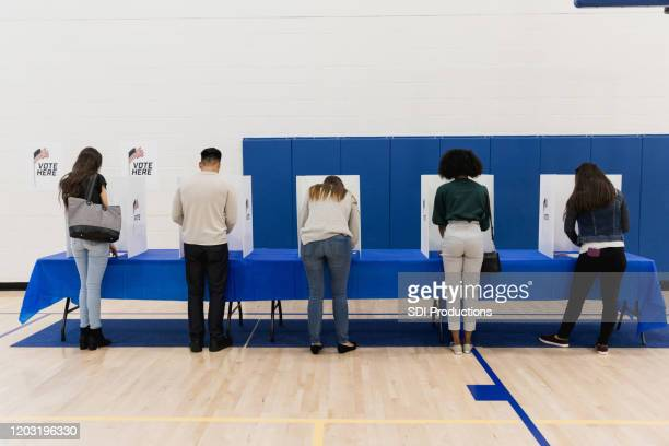 rear view photo five people casting ballots - democratic party usa stock pictures, royalty-free photos & images
