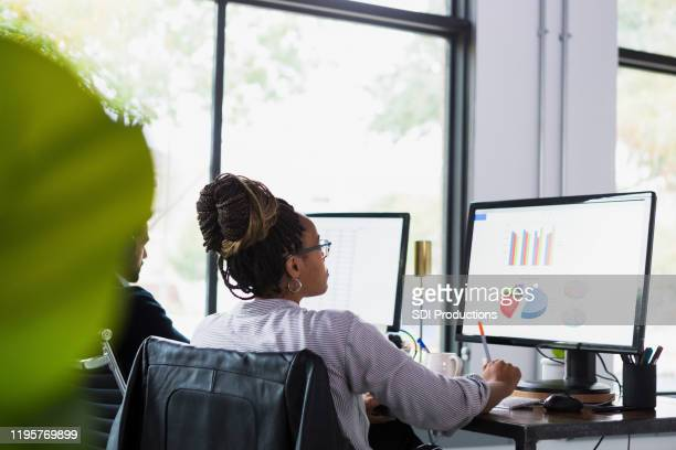 rear view photo of mid adult woman working on presentation - marketing stock pictures, royalty-free photos & images
