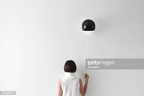 rear view portrait of a woman facing wall holding balloon - mimica fotografías e imágenes de stock
