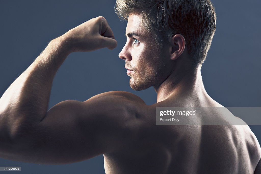 Rear view portrait of man flexing biceps muscles : Stock Photo