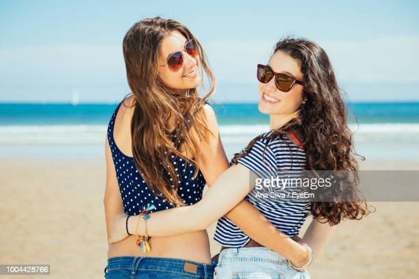 rear view portrait of smiling female friends wearing sunglasses while standing at beach - ピレネーアトランティーク ストックフォトと画像