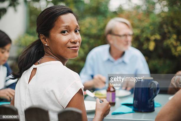 Rear view portrait of woman having food with family at outdoor table