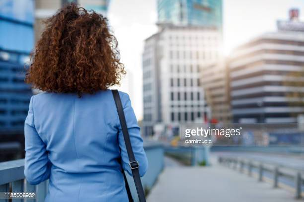 rear view portrait of young businesswoman communting to work - damircudic stock photos and pictures