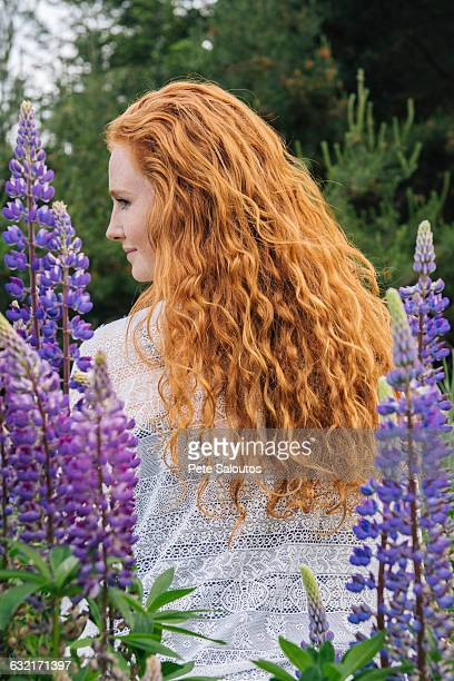 rear view portrait of young woman with long red hair amongst purple wildflowers - wavy hair stock pictures, royalty-free photos & images