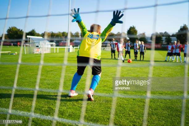 rear view professional young soccer goalkeeper viewed through goal net - goalkeeper stock pictures, royalty-free photos & images