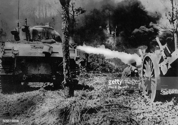 Rear view Sherman flamethrower in action. M4A3R3 Zippo: Sherman tank during the Battle of Okinawa . GI crouched alongside, Japan.