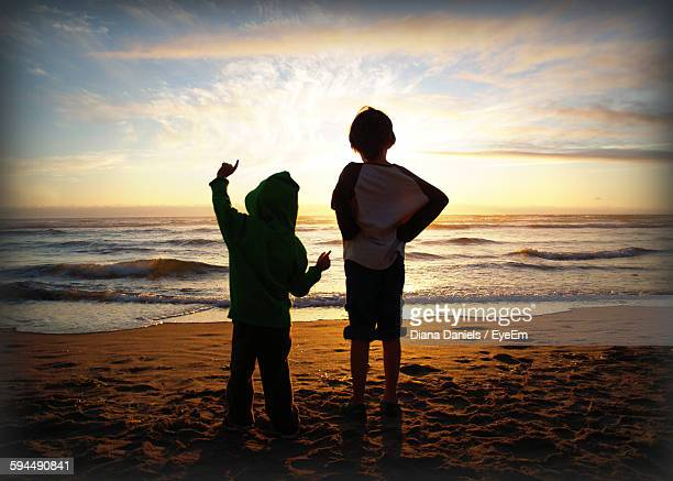 rear view siblings standing at beach against sky during sunset - diana daniels stock-fotos und bilder