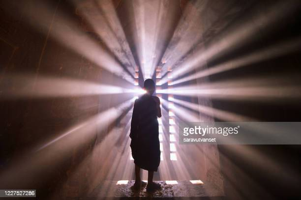 rear view silhouette of a novice monk standing by a window, mandalay, myanmar - spiritual enlightenment stock pictures, royalty-free photos & images