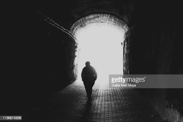 rear view silhouette of a senior man walking towards the light at the end of the tunnel - approaching stock pictures, royalty-free photos & images