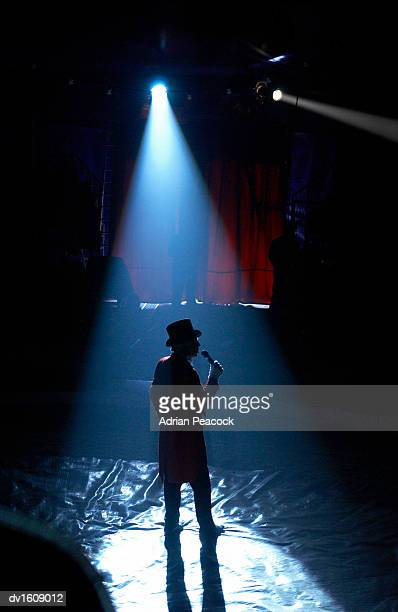 Rear View Silhouette of a Spot lit Ringmaster Standing in a Circus Ring, Talking into a Microphone