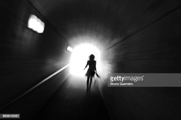 rear view silhouette of woman walking towards light at the end of tunnel - silhouette femme photos et images de collection