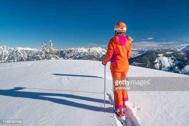 rear view skier woman walking in deep snow in beautiful mountains - ski holiday stock pictures, royalty-free photos & images