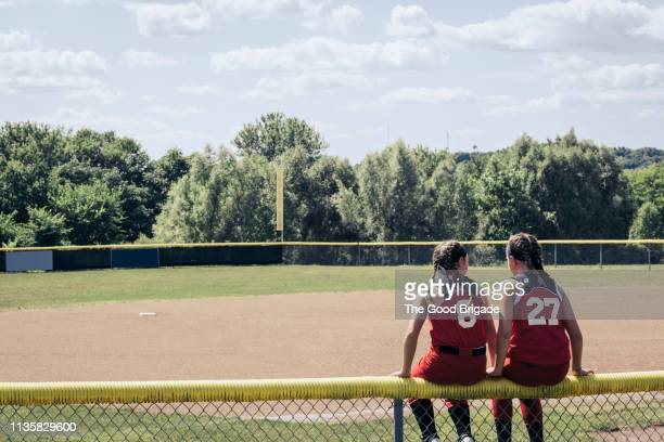 rear view softball players sitting on fence - softball sport stock pictures, royalty-free photos & images
