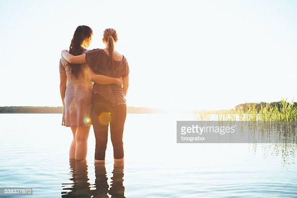 rear view, two young woman looking the sunset over lake