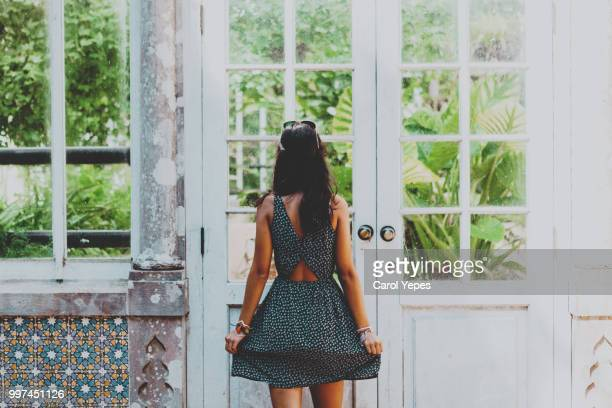 rear view woman standing in front greenhouse