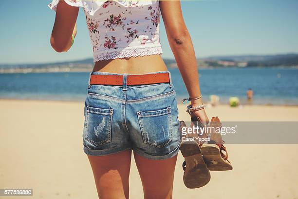 rear view  woman walking in beach.shots pants. - denim shorts stock pictures, royalty-free photos & images