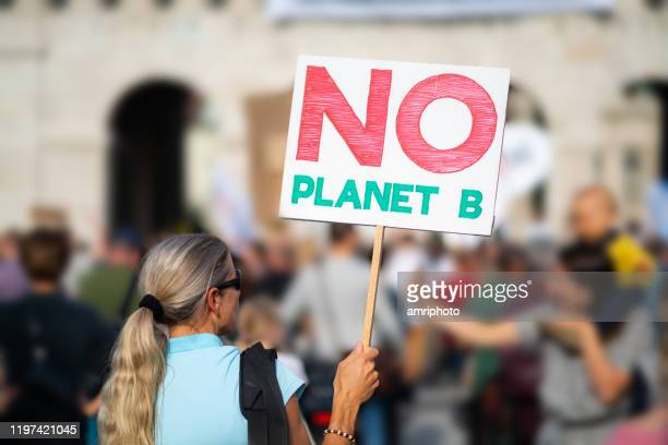 rear view woman with sign at climate change demonstration - climate stock pictures, royalty-free photos & images