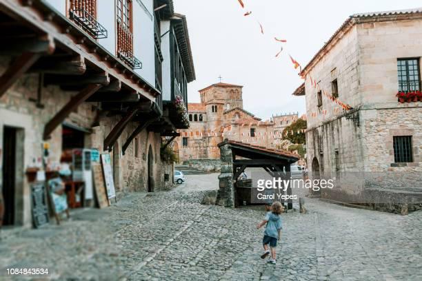 rear view young boy running in santillana del mar street,cantabria,spain - cantabria fotografías e imágenes de stock