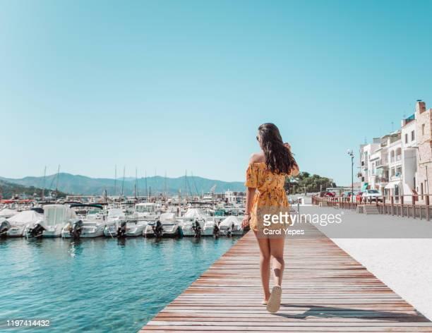 rear view young female walking on pier in catalonia,spain - mittelmeer stock-fotos und bilder