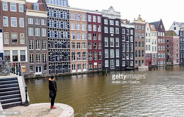 Rear View Young Man Standing By Canal Against Residential Buildings